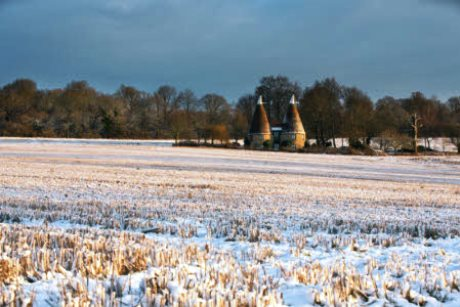 Oast houses on the snowy estate in January at Ightham Mote, Kent
